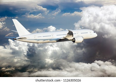 White passenger plane in flight. The plane is flying over the clouds.