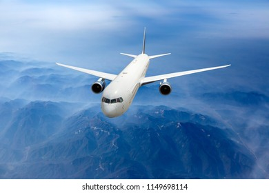 White passenger plane fly above the foggy mountain landscape. Front view of aircraft.