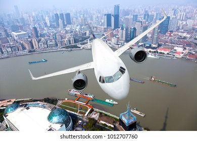 White passenger plane flyes above the buildings, city quarters and river. Front view.