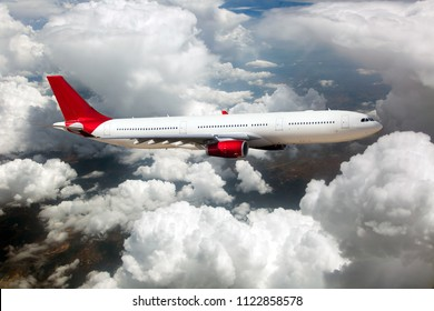 White passenger plane with red Tail in flight. The plane is flying over the clouds.