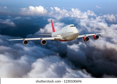 White passenger plane with red Tail in flight. Aircraft flying high in the sky above the clouds. Front view of airplane.