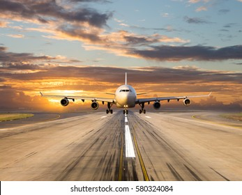 White passenger plane takes off from the airport runway. Aircraft moves against the backdrop of sunset sky. Airplane front view.