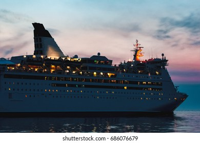 White passenger ship sailing in evening in still water
