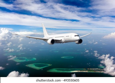 White passenger wide-body Dreamliner plane in flight. Aircraft is flying in blue cloudy sky over the sea and Maldivian islands and atolls.