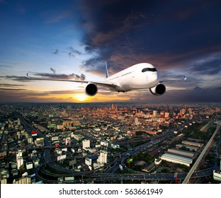 White passenger wide-body jet plane flies above urban landscape. Aircraft is flying high in the sunset cloudy sky, over the city residential areas and skyscrapers. Airplane front view.