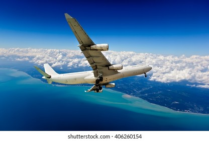 White passenger wide-body plane with 4 (four) Engines. Aircraft is flying in the cloudy sky, over the deep-blue ocean.