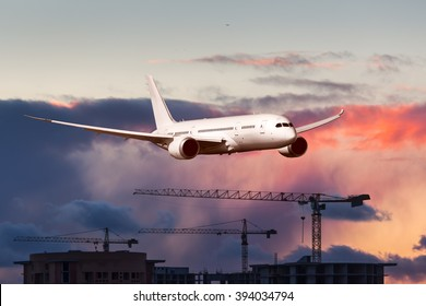White passenger wide-body plane. Aircraft is flying over the construction cranes with sunset sky at background.