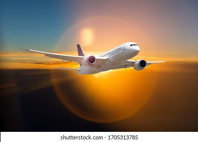 White passenger wide-body plane in flight. Aircraft flies above the clouds against the setting sun.