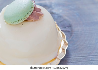 White pastry with green macaron.