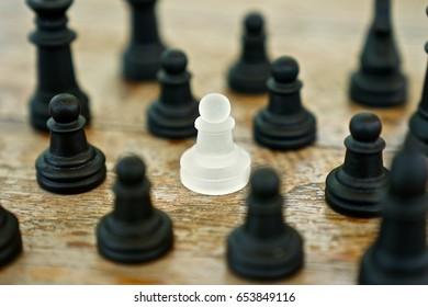 A white pawn is standing among all the black pieces.