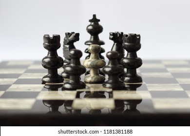White pawn surrounded by intimidating circle of black pieces on semi-reflective marble chess board against white background