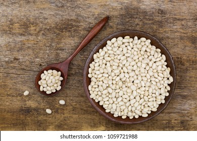 White pea beans, also called Navy bean, Pearl Haricot, Boston bean in clay bowl on wooden background, top view (Phaseolus vulgaris)