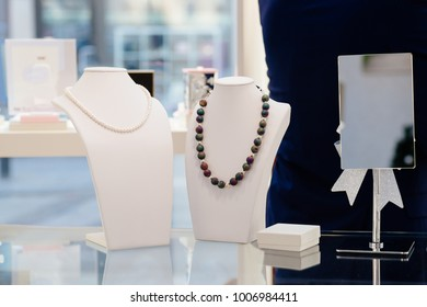 White pearl and agate stone luxury necklaces on neck stands display in a jewelry store