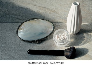 White pearl balls face powder for highlighting, makeup brushes on a gray background, top view, close up. Makeup accessories.