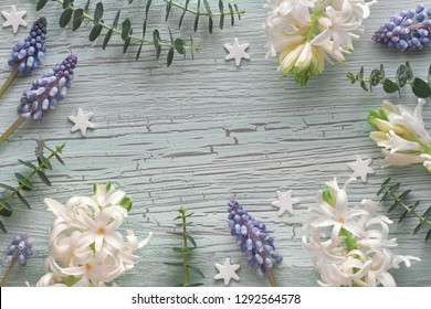 White pearl and blue grape hyacinth flowers with eucalyptus plants on light rustic textured wood, copy-space