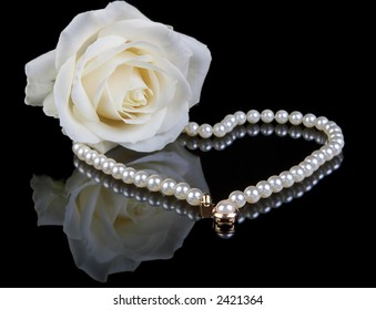 White pearl necklace and beautiful white rose on a black background - a valentine gift