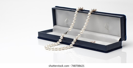 White pearl necklace in a black velvet box on isolated white background.