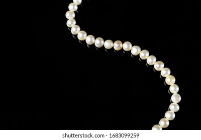 White pearls necklace on black background.