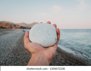 White pebble stone in hand on amazing landscape background at the beach in summer day. Travel and Vacation concept.