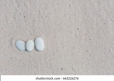 White pebbles, round small stones in a row on dry white sand beach, space for letters or text