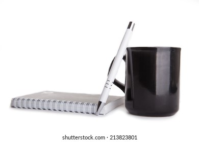 white pencil, notebook and black coffee cup isolated on white