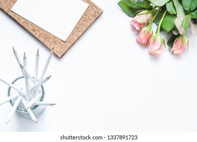 White pencils and pink roses