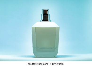 White perfume glass bottle on light blue background. Eau de toilette. Eau de parfum. Beautiful composition of perfume bottle