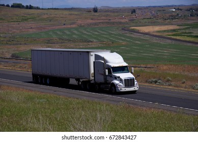 White Peterbilt Semi-Truck pulling a white unmarked trailer along a rural Oregon Highway.  June 20th, 2017 Rural Oregon, USA