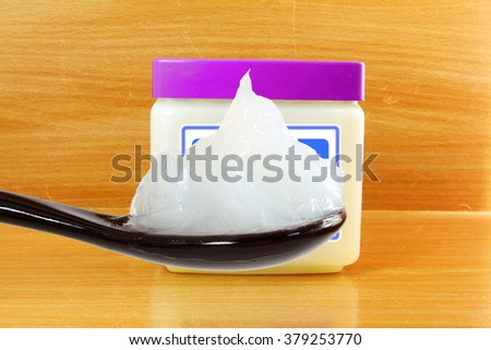 white petroleum jelly in spoon with jar