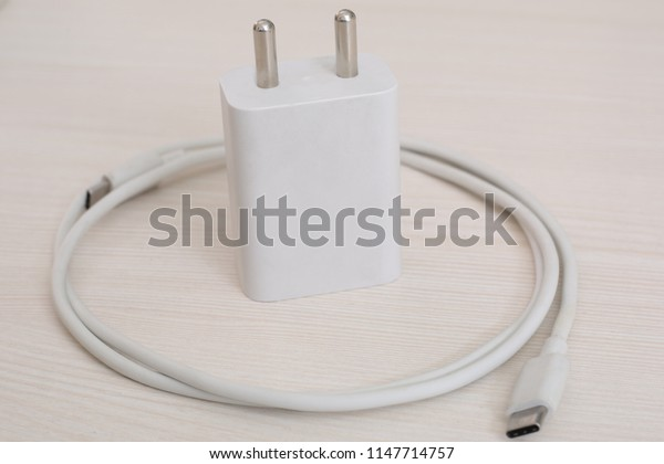 White Phone charger with White micro usb cable. Isolated on wooden background.