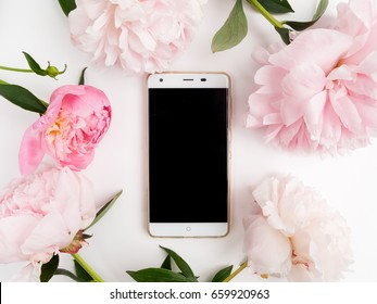 white phone with a clear screen on white background. peonies frame around. Flat lay. Top view
