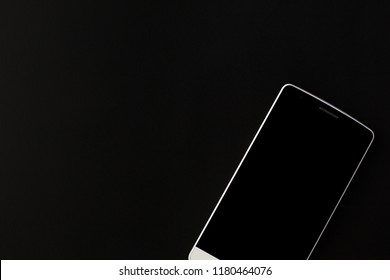 White phone lies on a black background.