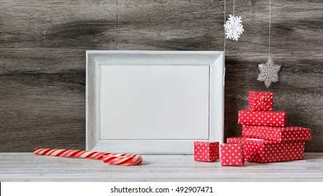 White photo frame with christmas decoration on the wooden table. Red boxes and snowflakes on the grey background. Frame for quotes. Christmas postcard.