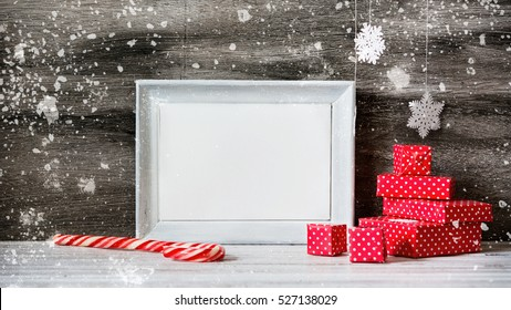 White photo frame with christmas decoration on the wooden table. Red boxes and snowflakes on the grey background. New year greeting card template. Holiday mock up. Scandinavian style.