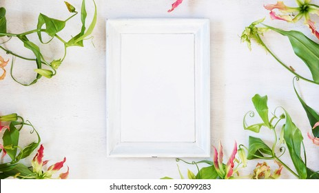 White photo frame with  orchids on the vintage table. Wedding decoration with text space. Frame for quotes. Tropical mock-up.