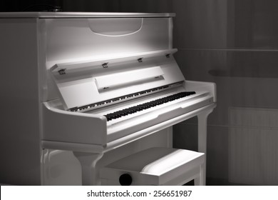 White piano in the dark. Piano chair