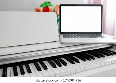 a white piano with a laptop on it. remote training, online education