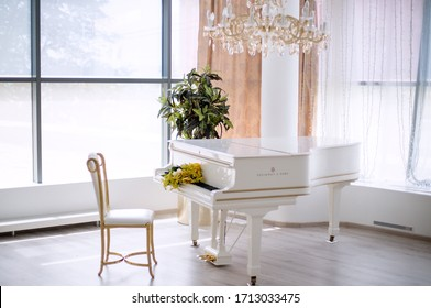 white piano standing in a large white room
