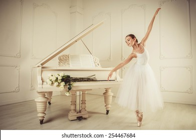 White piano stands in a large, bright interior, girl standing infront of it, she  She is dancing. on the piano keys are white roses.