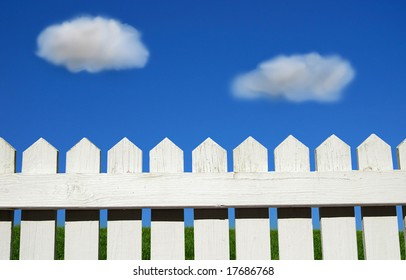 White picket fence, green grass and sky