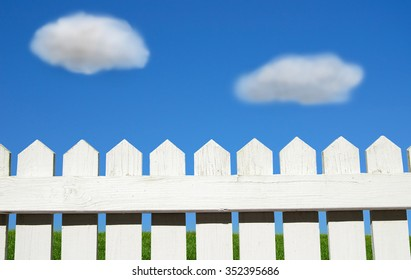 White picket fence, green grass and blue sky