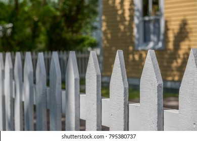 A white picket fence with a horizontal wooden rail. There's a yellow clapboard house with a white vertical window in the background.  There's a green tree in the upper left corner casting a shadow.