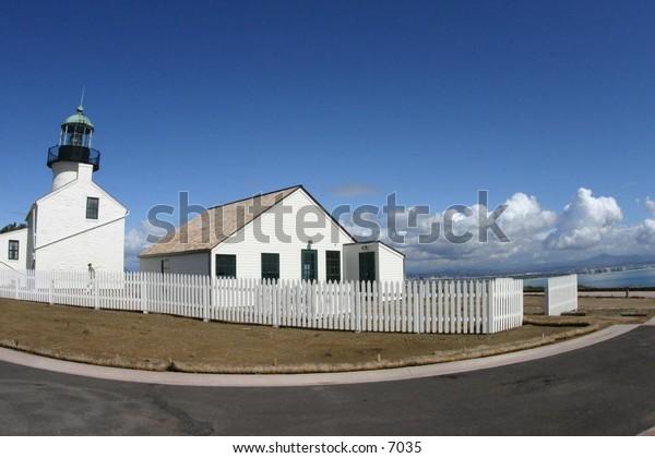 white picket fence surrounding lighthouse
