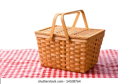 A white picnic basket on red gingham or checked tablecloth with a white background
