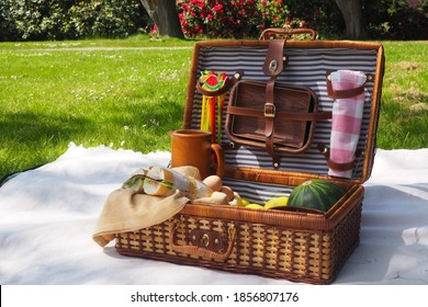 A white picnic blanket with a picnic basket on it, apples, watermelon, sandwiches in a basket. Green grass, trees and bushes in bloom on the background
