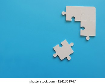 White pieces puzzle jigsaw on blue background.