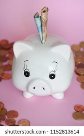 White piggy bank with banknotes and coins on pink background