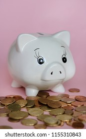 white piggy bank and coins on pink background