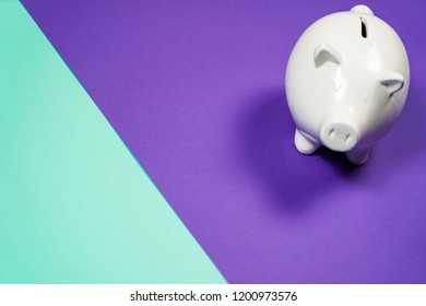 White Piggy bank isolated on purple background.