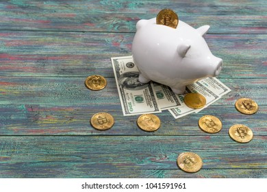 White piggy bank with one gold bitcoin coin new virtual money on a colored wooden background